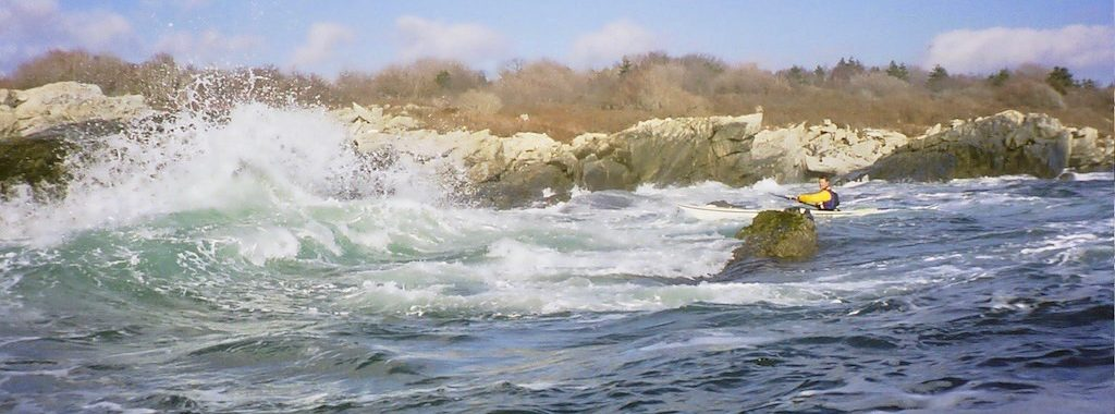 Sea kayaker going into rough surf by rocks